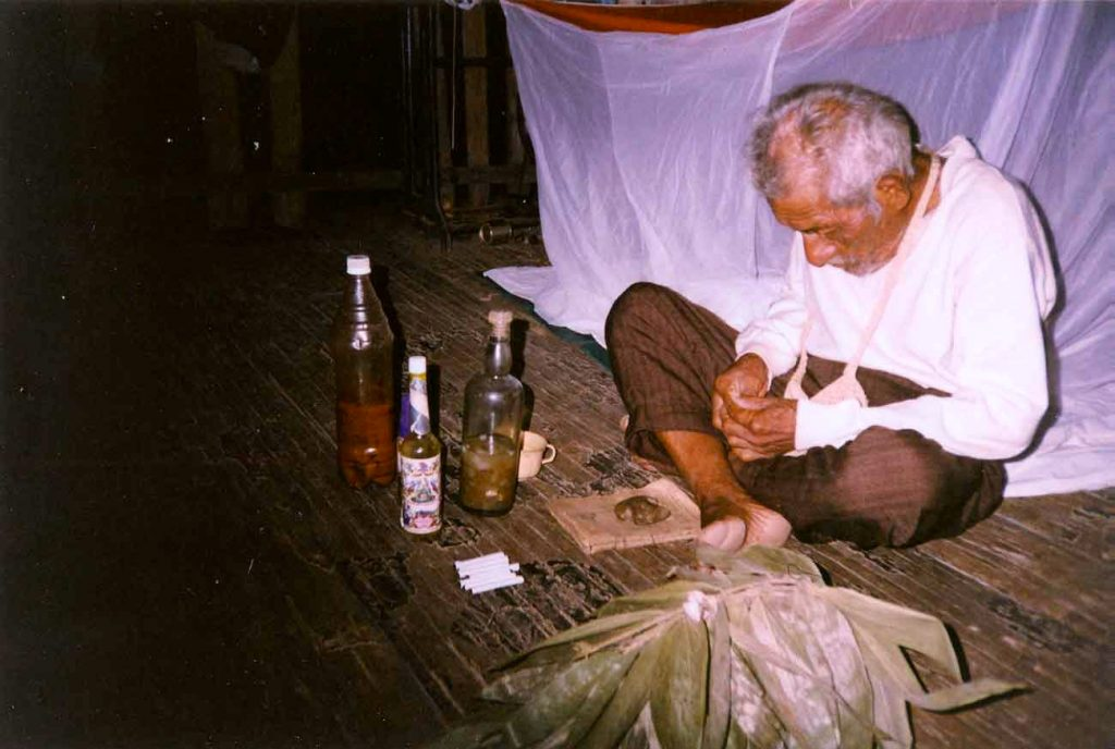 A rare picture of an Ayahuasca ceremony with Maestro Don Julio Llerena Pinedo, in 2001, in the Peruvian Amazon. Agua de florida, Mapacho cigars, Camphor, a Chakapa fan and a bottle of Ayahuasca are on the simple Mesa. Photo: C. Palazzolo © El Mundo Magico