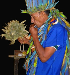 Taita Alfredo playing the harmonica during a Yage ritual. Photo: J. Imbachi Ⓒ El Mundo Magico