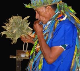 Taita Alfredo playing the harmonica during a Yage ritual. Photo: J. Imbachi Ⓒ El Mundo Magico